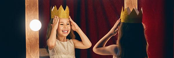 cours de théâtre pour enfants une petite fille se regarde dans un miroir avec une couronne sur la tête