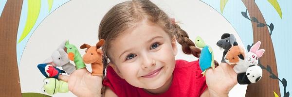 petite fille joue au théâtre avec des marionnettes